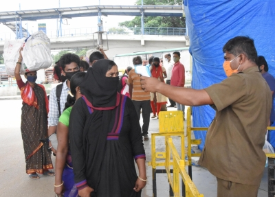 Bengaluru: Migrants being screened for the symptoms of COVID-19 as they arrive at a bus depot to head back to their native villages after the Bengaluru district authorities re-imposed lockdown across the city from Tuesday to July 22 for containing the corona virus spread, on July 13, 2020. (Photo: IANS)
