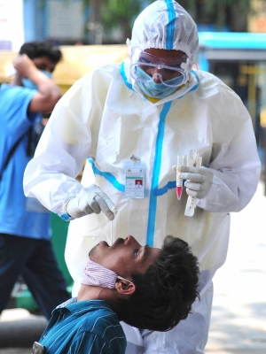 Bengaluru: A medic collects swab samples for COVID-19 test, amid surge in corona virus cases across the country, in Bengaluru On Sunday, 18th 2021.(Photo:Dhananjay Yadav/IANS)